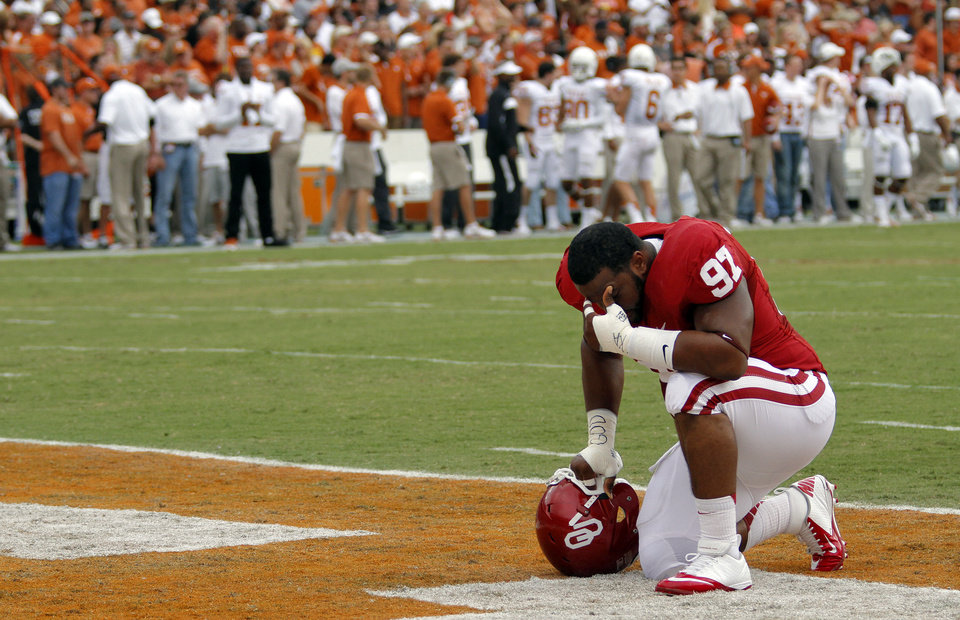 Photo - OU's Jamarkus McFarland (97) kneels in prayer during the Red River Rivalry college football game between the University of Oklahoma (OU) and the University of Texas (UT) at the Cotton Bowl in Dallas, Saturday, Oct. 13, 2012. Photo by Chris Landsberger, The Oklahoman