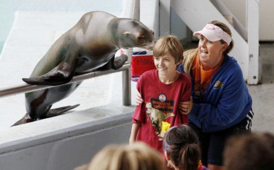Dillon Bruce, 11, of Oklahoma City, gets a kiss from a sea lion with help from trainer Shannon Charles-Ray during a show at the Oklahoma City Zoo. <strong>PAUL B. SOUTHERLAND - THE OKLAHOMAN</strong>