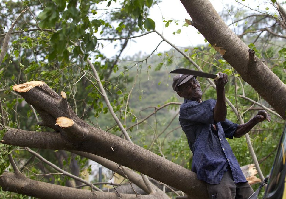 An elderly gentleman clears a tree from the road in Jacmel, Haiti, a day after Tropical Storm Isaac brought rains and winds across the nation, Sunday, Aug. 26, 2012. At least seven people were killed by flooding in Haiti, including in tent cities filled with earthquake victims, and two others in the Dominican Republic. (AP Photo/The Miami Herald, Patrick Farrell)  ORG XMIT: FLMIH108