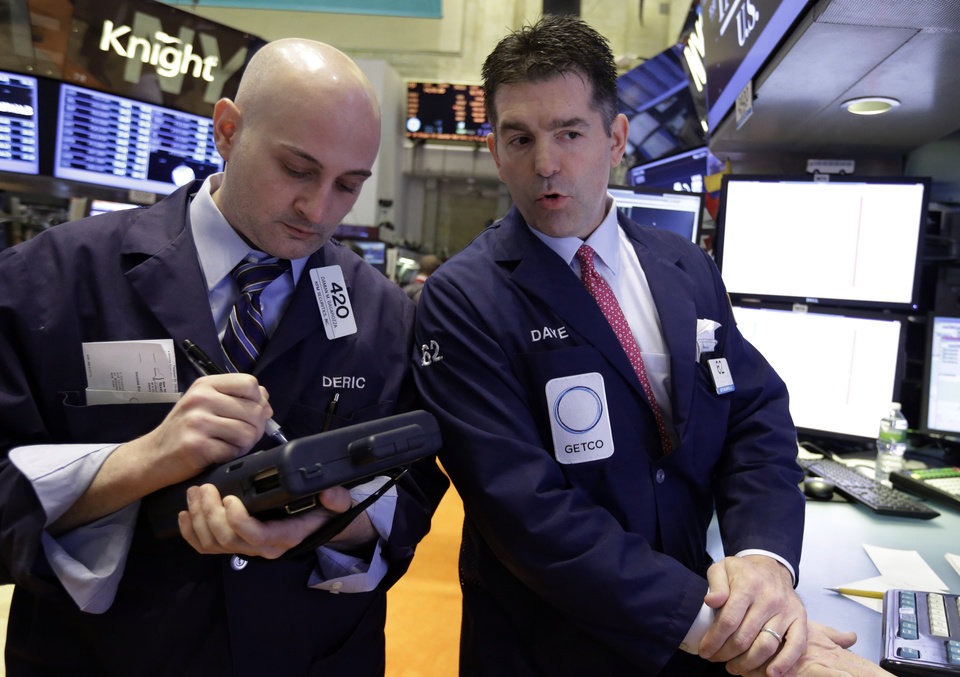 Photo - Trader Damian Bagarozza, left, and specialist David Haubner work on the floor of the New York Stock Exchange Thursday, May 2, 2013. Stocks are opening higher on Wall Street, a day after the market's biggest fall in two weeks, after General Motors and other big companies announced higher profits. (AP Photo/Richard Drew)