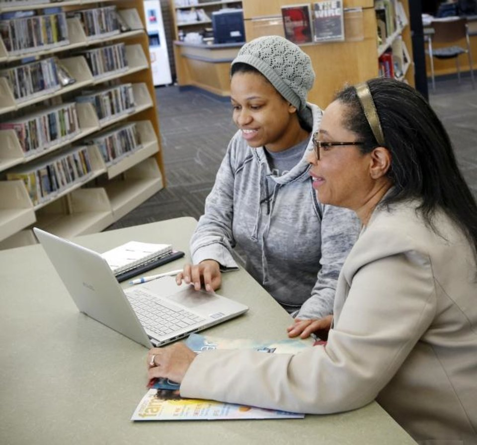 Photo -  LaTwyla Guess, right, talks to her daughter Michelle Thomas about a college project Thomas came to work on at the Ralph Ellison Library, 2000 NE 23, in Oklahoma City, Friday, Feb. 7, 2020. [Nate Billings/The Oklahoman]