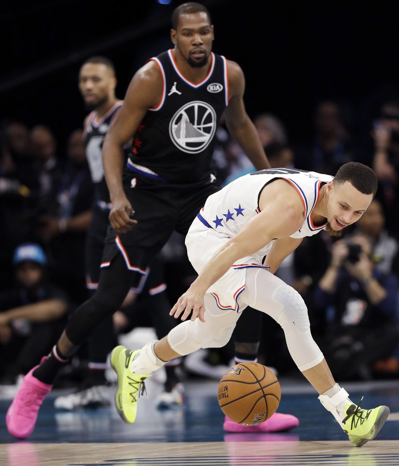 Photo - Team Giannis' Stephen Curry, of the Milwaukee Bucks, works for a loose ball against Team LeBron during the second half of an NBA All-Star basketball game, Sunday, Feb. 17, 2019, in Charlotte, N.C. The Team LeBron won 178-164. (AP Photo/Chuck Burton)
