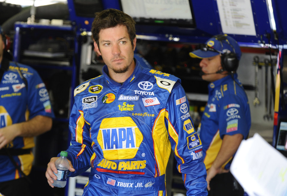 Martin Truex, Jr. walks in the garage during practice for the NASCAR Sprint Cup Series auto race at Texas Motor Speedway, Friday, April 13, 2012, in Fort Worth, Texas. (AP Photo/Ralph Lauer) ORG XMIT: TMS124