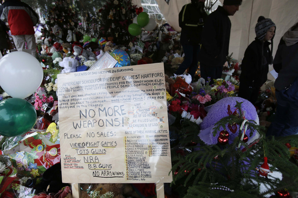 A sign against weapons is displayed at a memorial to the Newtown shooting victims in the Sandy Hook village of Newtown, Conn., Saturday, Dec. 22, 2012. The funerals for the victims of the school shooting are wrapping up after a wrenching week of farewells. Twenty children and six adults were killed at Sandy Hook Elementary School on Dec. 14. Adam Lanza, the lone gunman, killed his mother before going on the rampage and then committed suicide. (AP Photo/Seth Wenig)