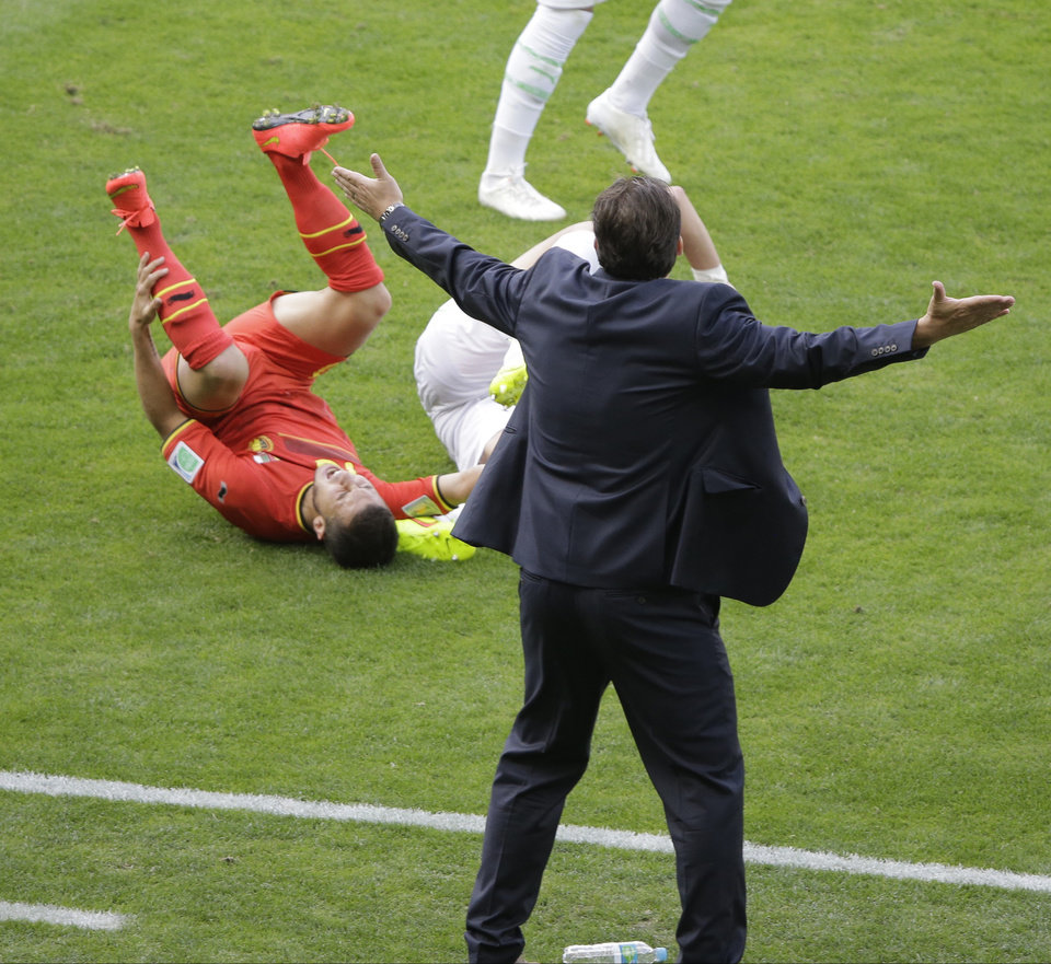 Photo - Belgium's head coach Marc Wilmots reacts as Belgium's Eden Hazard grimaces in pain after colliding with an Algerian player during the group H World Cup soccer match between Belgium and Algeria at the Mineirao Stadium in Belo Horizonte, Brazil, Tuesday, June 17, 2014.  (AP Photo/Sergei Grits)