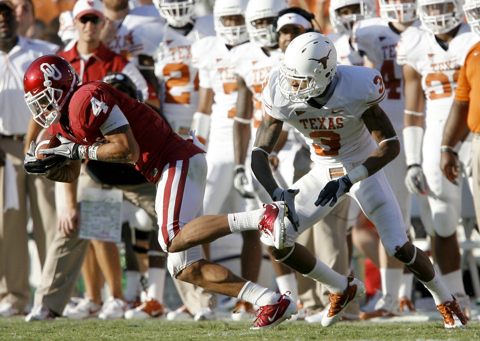 Photo - OU's Kenny Stills catches a pass for a furst down in front Texas' Curtis Brown Texas during the second half of the Red River Rivalry college football game between the University of Oklahoma Sooners (OU) and the University of Texas Longhorns (UT) at the Cotton Bowl on Saturday, Oct. 2, 2010, in Dallas, Texas. OU coach Bob Stoops applauds his team during the second half of the Red River Rivalry college football game between the University of Oklahoma Sooners (OU) and the University of Texas Longhorns (UT) at the Cotton Bowl on Saturday, Oct. 2, 2010, in Dallas, Texas.  OU defeated Texas 28-20.    Photo by Bryan Terry, The Oklahoman