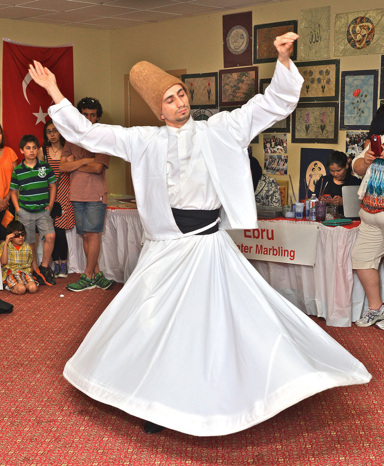 Photo -  Whirling dervish Kamil Tekelogia, from Turkey, performs Saturday during the Turkish Festival presented by the Raindrop Foundation in Oklahoma City. Photo by M. Tim Blake, for The Oklahoman   M. Tim Blake