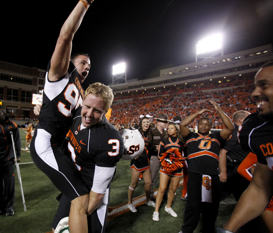 Photo - OSU's Brandon Weeden (3) lifts kicker Dan Bailey in the air following the college football game between Texas A&M University (TAMU) and Oklahoma State University (OSU) at Boone Pickens Stadium in Stillwater, Okla., Thursday, Sept. 30, 2010. Photo by Sarah Phipps, The Oklahoman