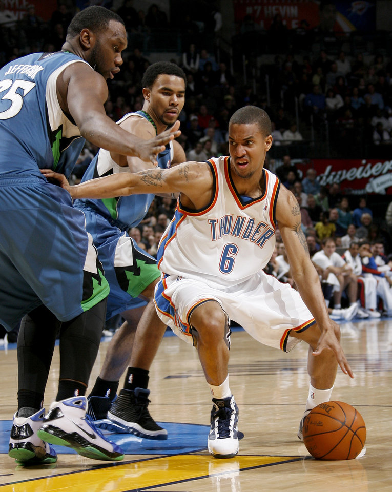 Photo - Oklahoma City's Eric Maynor drives by Minnesota's Al Jefferson, left, and Ramon Sessions during the NBA basketball game between the Oklahoma City Thunder and the Minnesota Timberwolves, at the Ford Center in Oklahoma City, Friday, Feb. 26, 2010.  Photo by Bryan Terry, The Oklahoman ORG XMIT: KOD