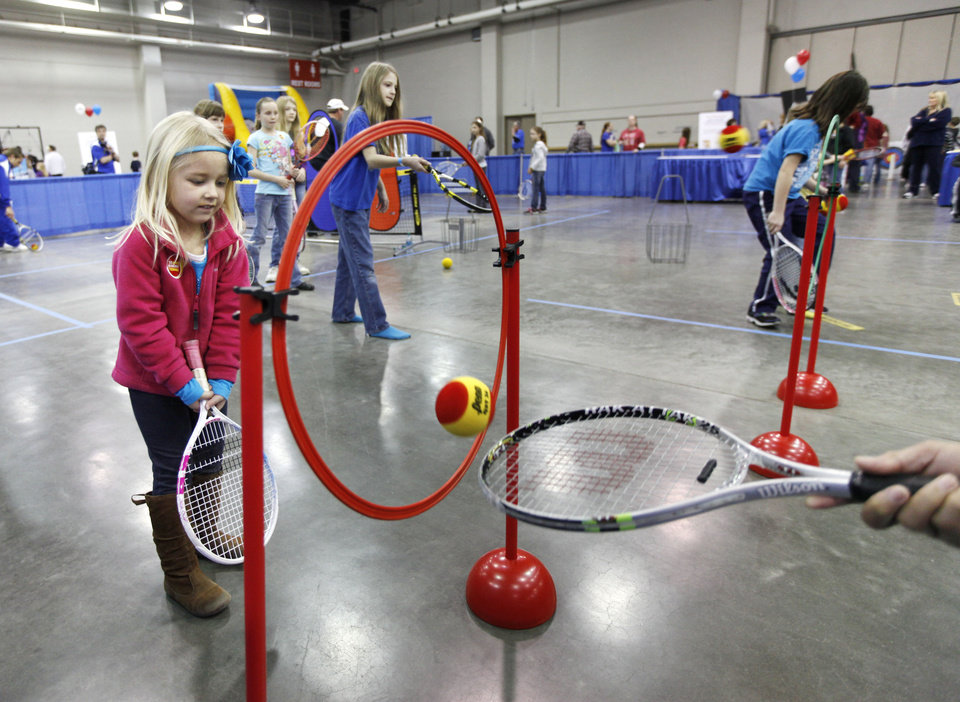 Photo - Children learn some tennis skills during Bart & Nadia's Sports & Health Festival at the Cox Convention Center in Oklahoma City, OK, Saturday, February 16, 2013,  By Paul Hellstern, The Oklahoman