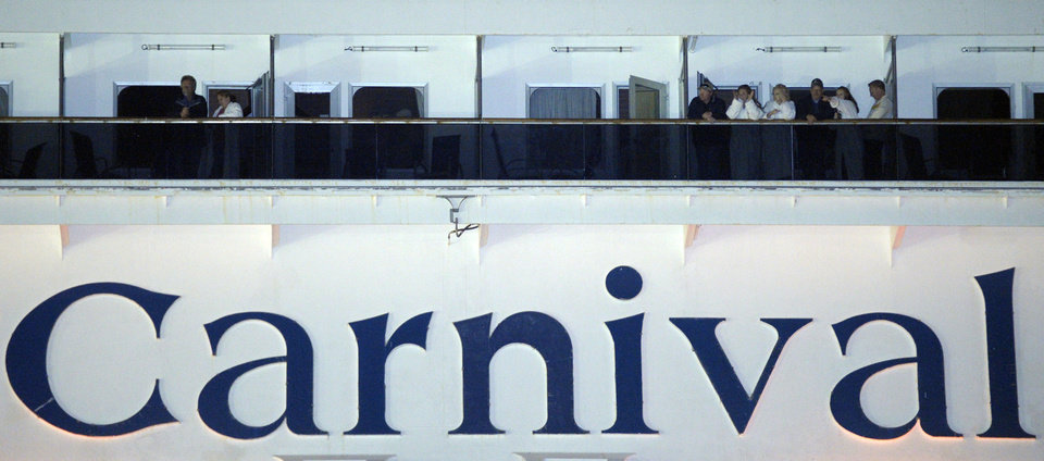 Photo - People watch from their balconies aboard the Carnival Triumph after it was towed to the cruise terminal in Mobile, Ala., Thursday, Feb. 14, 2013. The ship with more than 4,200 passengers and crew members idled for nearly a week in the Gulf of Mexico following an engine room fire. (AP Photo/G M Andrews)
