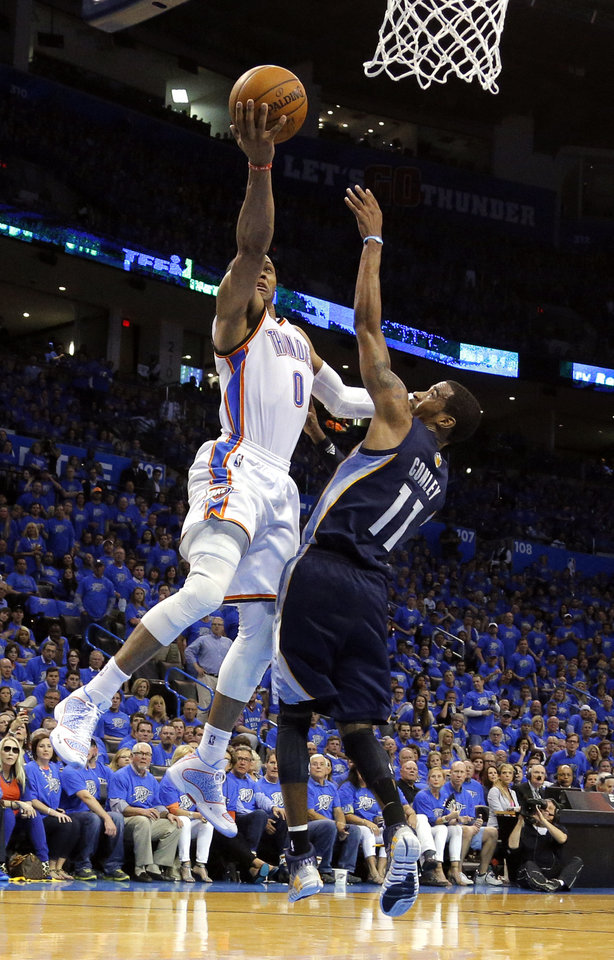 Photo - Oklahoma City 's Russell Westbrook (0) shoots a lay up over Memphis' Mike Conley (11) during Game 1 in the first round of the NBA playoffs between the Oklahoma City Thunder and the Memphis Grizzlies at Chesapeake Energy Arena in Oklahoma City, Saturday, April 19, 2014. Photo by Sarah Phipps, The Oklahoman