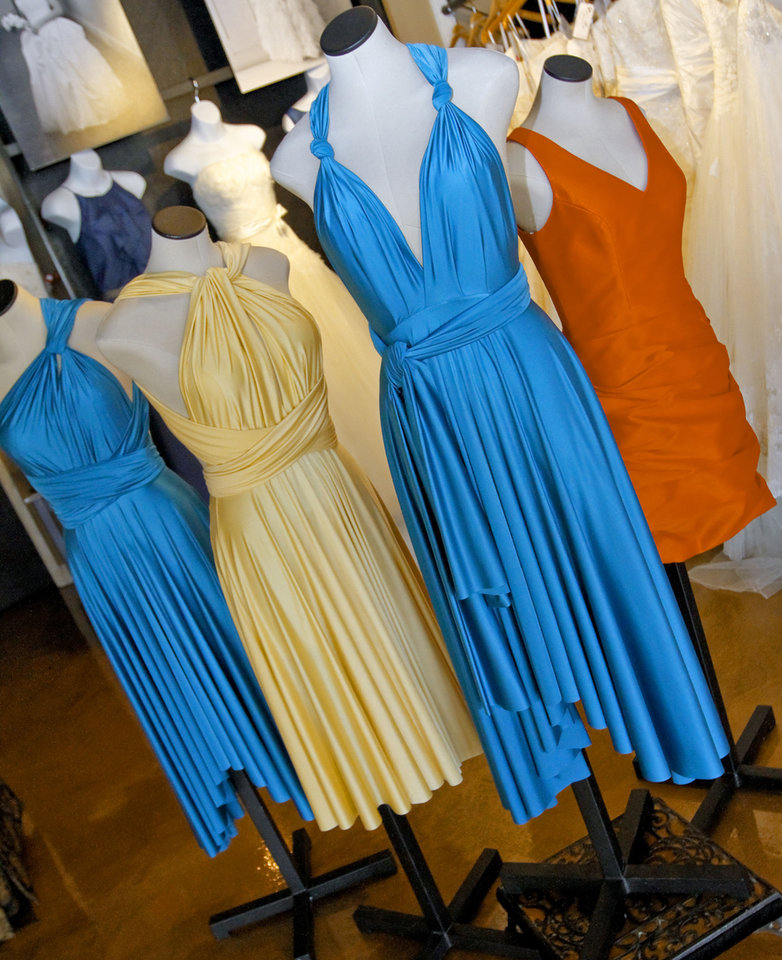 Photo - The three wrap dresses on left are by Two Birds. They are all the same dress, wrapped different ways. At right is a dress by Jim Hjelm Occasions. Together, they create the perfect color palette for a Thunder-themed wedding party. Dresses are sold at Meg Guess Couture Bridal Shop. Photo by Chris Landsberger, The Oklahoman.  CHRIS LANDSBERGER