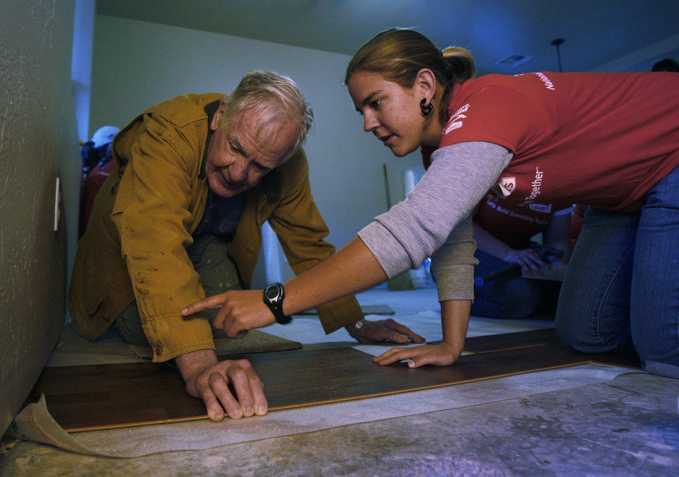 Photo - Wake Bowser and Mindy Sprecker work on flooring at a Habitat for Humanity house at 313 East Himes Street in Norman, Okla. on May 2, 2009.  Photo by Steve Sisney, The Oklahoman