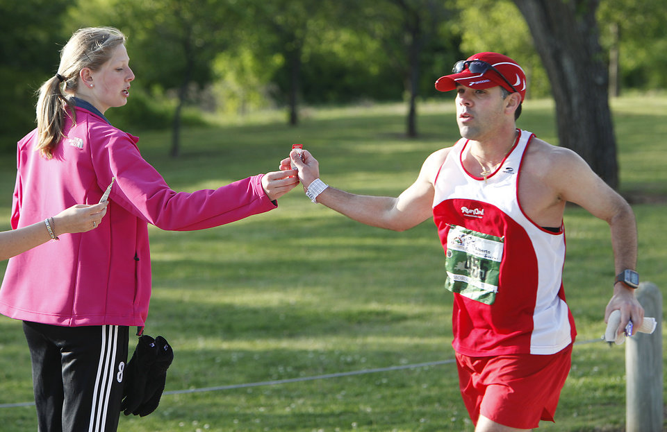 Photo - Megan Fay, 14, hands an energy gel to runner Alberto Gutierrez in Stars and Stripes Park  during the Tenth Annual Oklahoma City Memorial Marathon, Sunday, April 25, 2010.  Photo by David McDaniel, The Oklahoman ORG XMIT: KOD