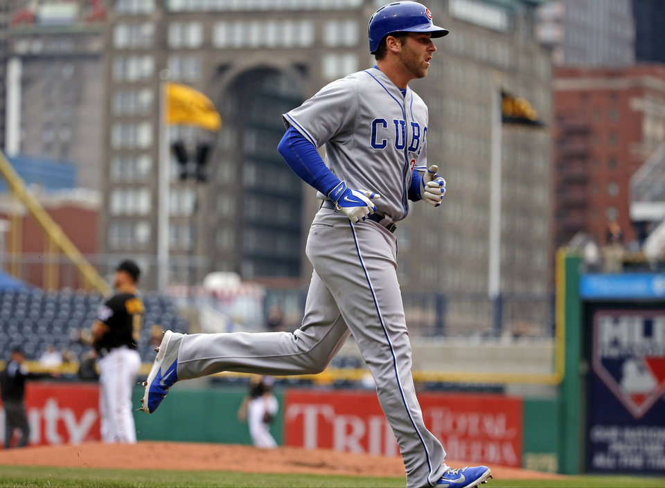 Photo - Chicago Cubs' Mike Olt rounds third after hitting a solo-home run off Pittsburgh Pirates starting pitcher Wandy Rodriguez, left rear, during the second inning of a baseball game in Pittsburgh Thursday, April 3, 2014. (AP Photo/Gene J. Puskar)