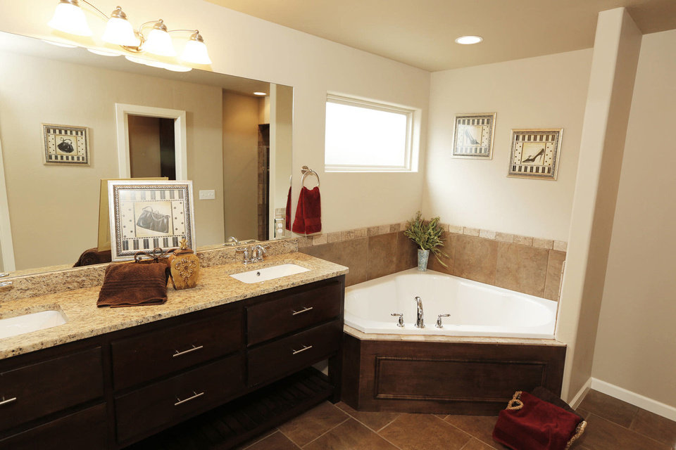 Photo - LEFT: Natural light illuminates the large corner tub in the TimberCraft model's master bath.  Photos by Steve Gooch, The Oklahoman