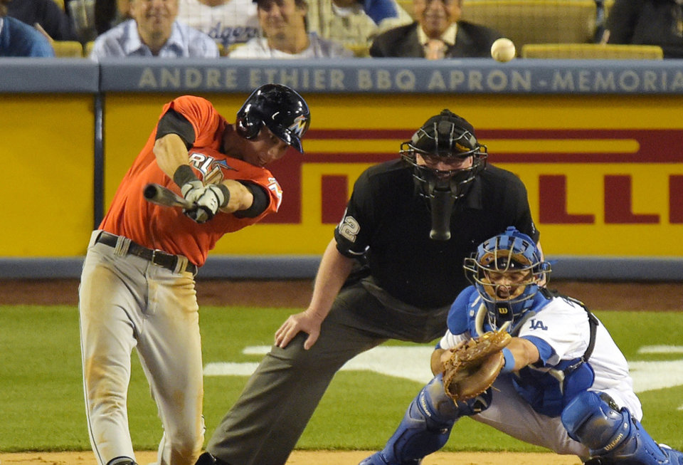 Photo - Miami Marlins' Christian Yelich, left, hits a solo home run as Los Angeles Dodgers catcher Drew Butera catches and home plate umpire Gerry Davis looks on during the third inning of a baseball game, Monday, May 12, 2014, in Los Angeles. (AP Photo)