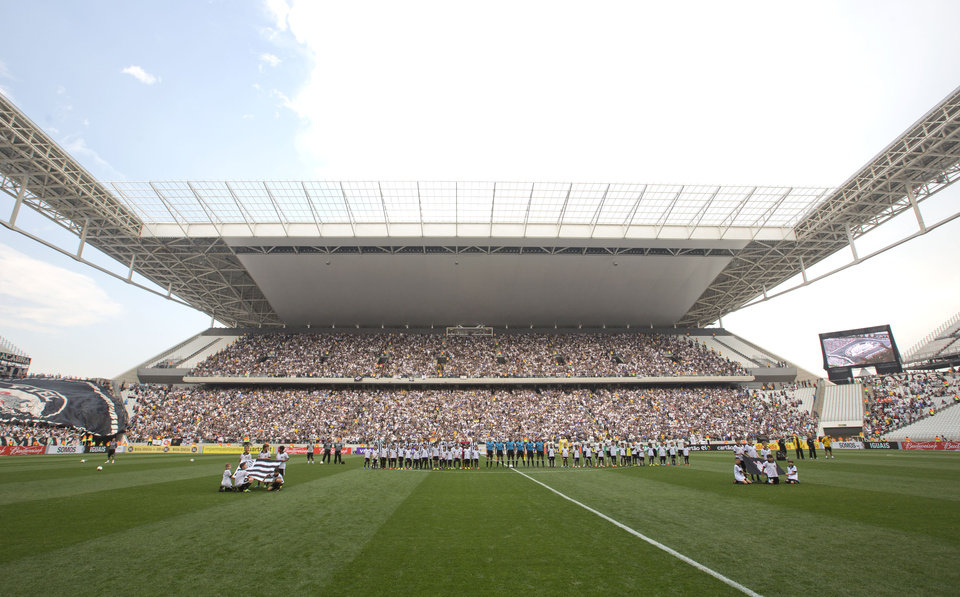 Photo - Corinthians's and  Figueirense players listen to the national anthem prior to a Brazilian soccer league match at the Itaquerao, the still unfinished stadium that will host the World Cup opener match between Brazil and Croatia on June 12, in Sao Paulo, Brazil, Sunday, May 18, 2014. Only 40,000 tickets were put on sale for Corinthians' match against Figueirense because some of the 20,000 temporary seats needed for the World Cup opener are still being installed. (AP Photo/Andre Penner)