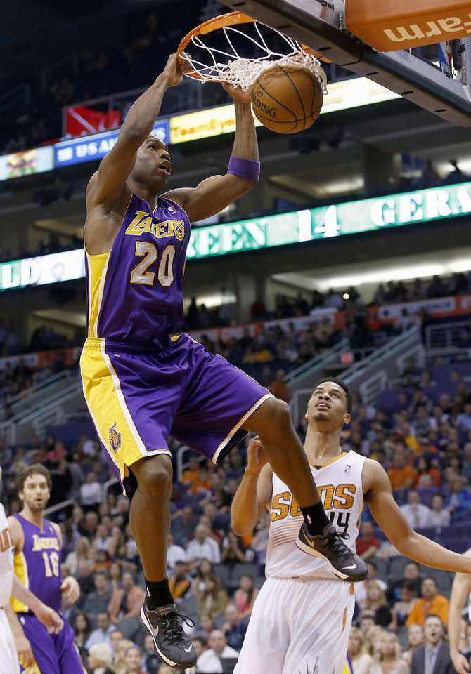 Photo - Los Angeles Lakers' Jodie Meeks (20) dunks as he gets past Phoenix Suns' Gerald Green, right, during the first half of an NBA basketball game Wednesday, Jan. 15, 2014, in Phoenix. (AP Photo/Ross D. Franklin)