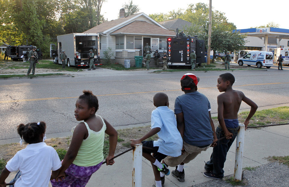 Photo -   Neighborhood children watch as members of the Madison County tactical response team secure a house Thursday evening, Aug. 23, 2012 in Washington Park, Ill. A teenage girl reported missing more than two years ago escaped from the Southwestern Illinois home where she said she was held captive and repeatedly sexually assaulted, police said Thursday. Police in Washington Park, a village next to East St. Louis, said the girl reported that she was raped by her captor, got pregnant and had a baby. (AP Photo/St. Louis Post-Dispatch, J.B. Forbes) EDWARDSVILLE INTELLIGENCER OUT; THE ALTON TELEGRAPH OUT