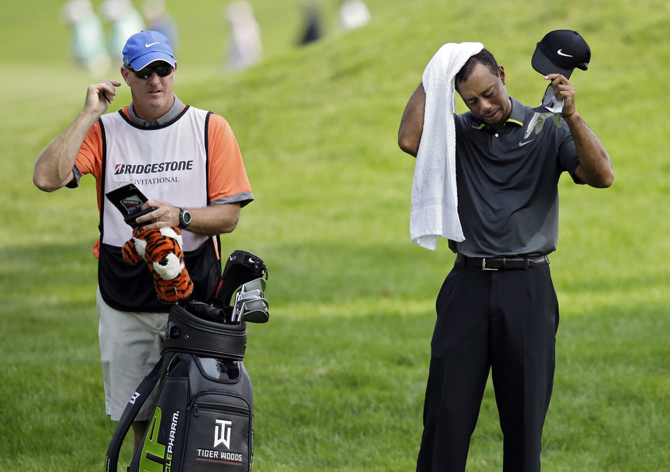Photo - Tiger Woods wipes his head as he waits to hit to the 10th green with caddie Joe Lacava, left, during the second round of the Bridgestone Invitational golf tournament Friday, Aug. 1, 2014, at Firestone Country Club in Akron, Ohio. (AP Photo/Mark Duncan)