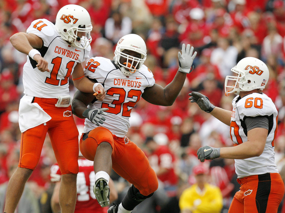 Photo - OSU's Zac Robinson (11), Julius Crosslin (32) and Brady Bond (60) celebrate a touchdown by Crosslin in the second quarter during the college football game between Oklahoma State University (OSU) and the University of Nebraska (NU) at Memorial Stadium in Lincoln, Neb., Saturday, October 13, 2007. By Nate Billings, The Oklahoman