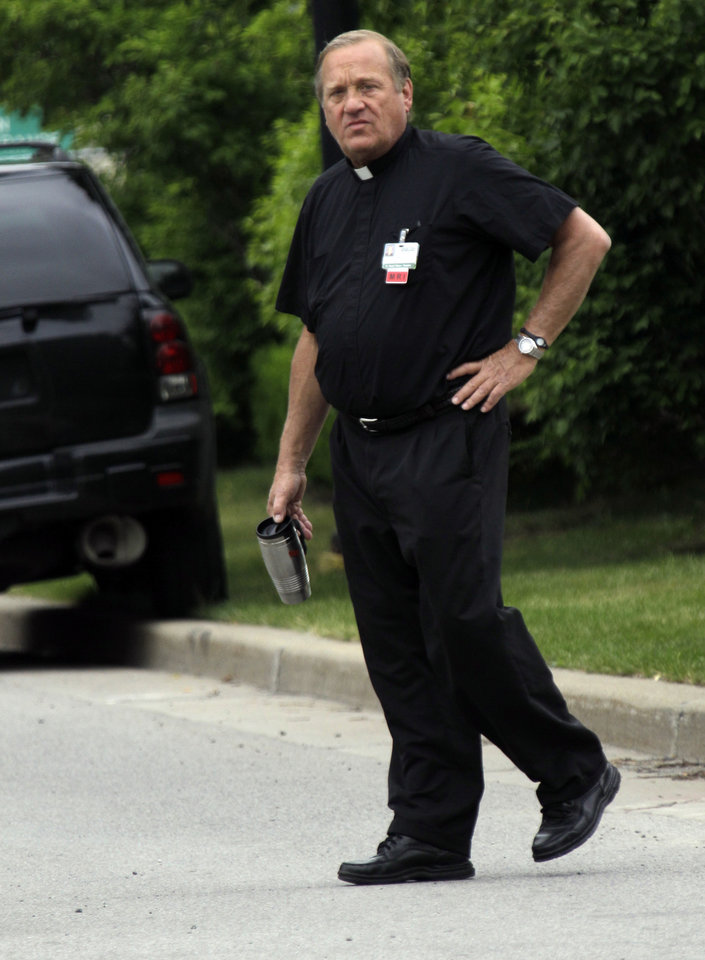 Photo -   A priest walks near the scene of a shooting at Erie Count Medical Center in Buffalo, N.Y., Wednesday, June 13, 2012. A police official confirms that a woman was killed Wednesday morning on the grounds of the Erie County Medical Center, which he describes as being in