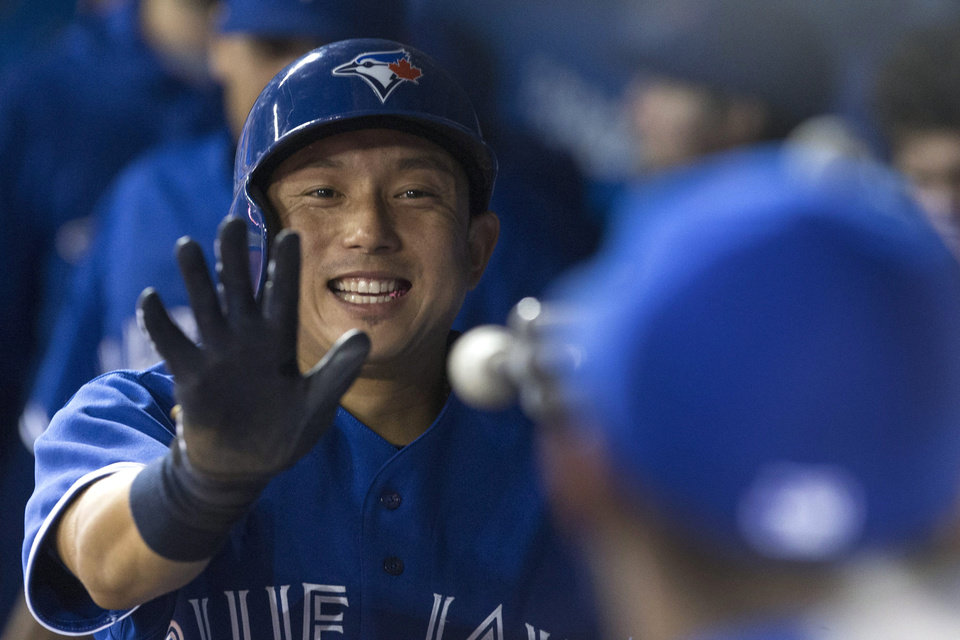 Photo - Toronto Blue Jays Munenori Kawasaki celebrates in the dugout after scoring on an Edwin Encarnacion double off New York Yankees starting pitcher Ivan Nova during first inning MLB American League baseball action in Toronto on Sunday April 21, 2013. (AP Photo/The Canadian Press, Chris Young)