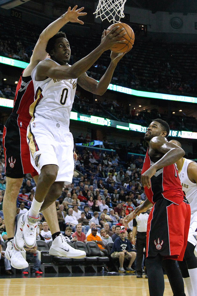 Photo - New Orleans Pelicans forward Al-Farouq Aminu (0) drives to the basket against Toronto Raptors forward Amir Johnson, right, and forward Tyler Hansbrough, left, during the second half of an NBA basketball game in New Orleans, Wednesday, March 19, 2014. The Raptors won 107-100. (AP Photo/Jonathan Bachman)