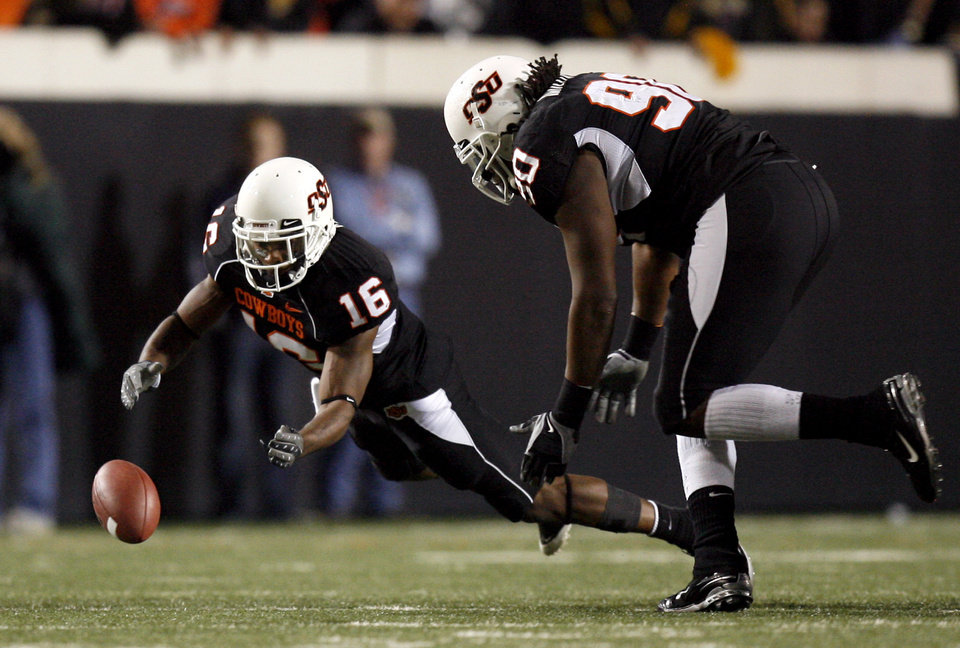 Photo - OSU's Perrish Cox (16) recovers a fumble as Swanson Miller (90) looks on during the college football game between Oklahoma State University (OSU) and the University of Colorado (CU) at Boone Pickens Stadium in Stillwater, Okla., Thursday, Nov. 19, 2009. Photo by Sarah Phipps, The Oklahoman