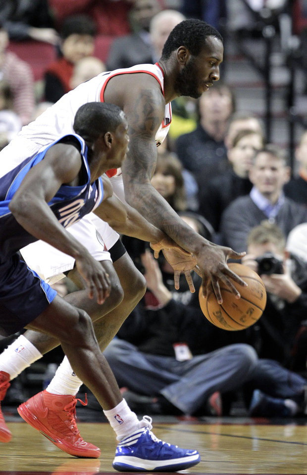 Dallas Mavericks guard Darren Collison, left, and Portland Trail Blazers center J.J. Hickson chase down a loose ball during the first quarter of an NBA basketball game in Portland, Ore., Tuesday, Jan. 29, 2013.(AP Photo/Don Ryan)