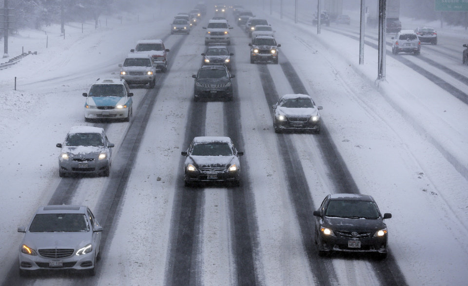 Photo - Motorists drive along a snow covered northbound Interstate-94 in Chicago on Sunday, Jan. 5, 2014. Sunday night temperatures will drastically drop to about minus 20 degrees. (AP Photo/Nam Y. Huh)