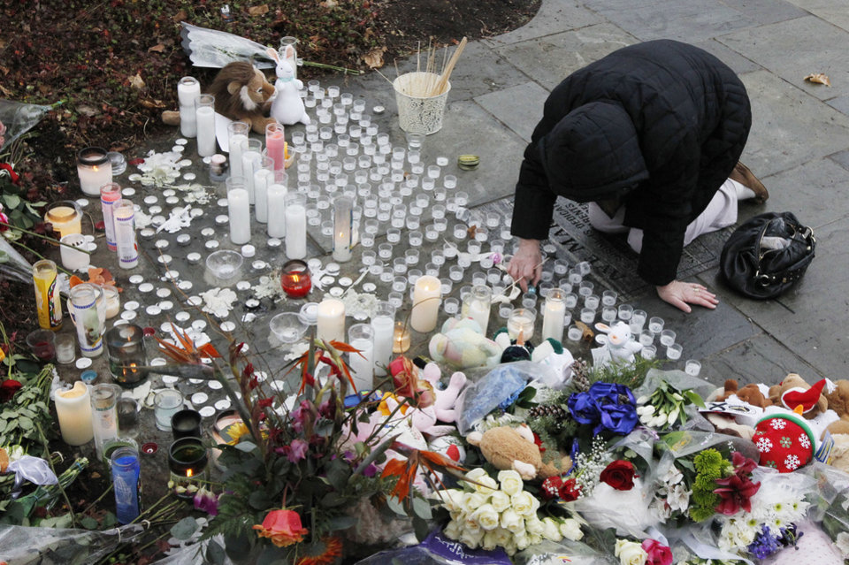 Photo - A woman pays respects at a memorial outside of St. Rose of Lima Roman Catholic Church, Sunday, Dec. 16, 2012, in Newtown, Conn. On Friday, a gunman allegedly killed his mother at their home and then opened fire inside the Sandy Hook Elementary School in Newtown, killing 26 people, including 20 children. (AP Photo/Julio Cortez)