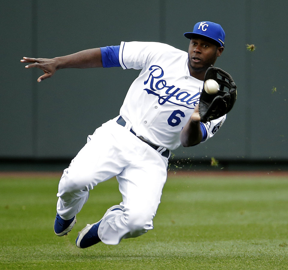 Photo - Kansas City Royals' Lorenzo Cain catches a fly ball for the out on Chicago White Sox's Jose Abreu during the fifth inning of a home opener baseball game Friday, April 4, 2014, in Kansas City, Mo. (AP Photo/Charlie Riedel)