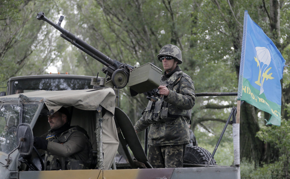 Photo - Ukrainian army paratroopers move to a position in Slovyansk, Ukraine, Monday, June 2, 2014. Hundreds of armed insurgents attacked a border guards' camp in eastern Ukraine Monday, as rebels nearby promised safety for the officers if they surrendered the base and lay down their arms. (AP Photo/Efrem Lukatsky)