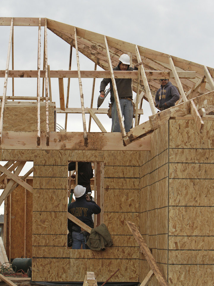 Photo - Workers frame a house by Home Creations at 2344 NW 196.  David McDaniel - The Oklahoman