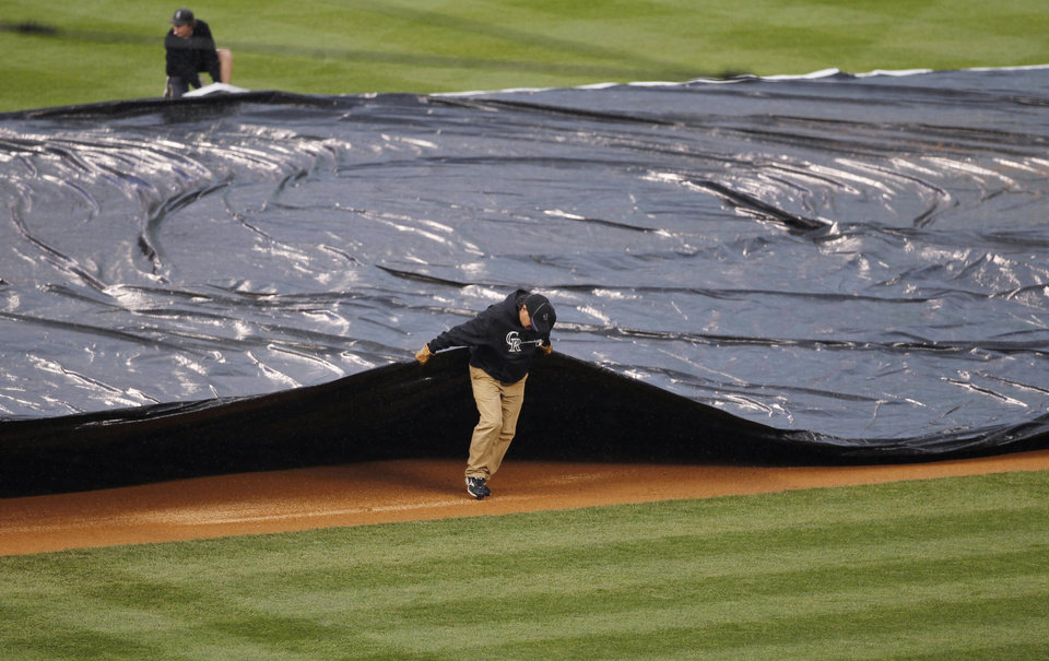 Field crew members pull the tarpaulin as heavy rains sweep over Coors Field and halt play in the fourth inning of a baseball game between the New York Yankees and Colorado Rockies in Denver on Thursday, May 9, 2013. (AP Photo/David Zalubowski)