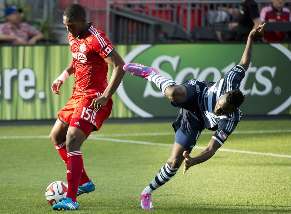 Photo - Toronto FC defender Doneil Henry, left, battles for the ball against Sporting Kansas City forward C.J. Sapong during the first half of an MLS soccer game Saturday, July 26, 2014, in Toronto. (AP Photo/The Canadian Press, Nathan Denette)