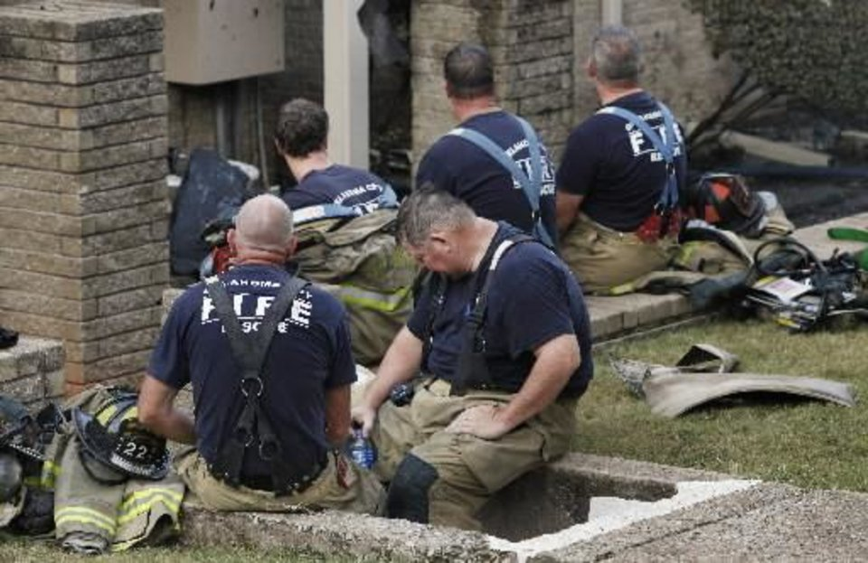 Firemen take a rest to catch their breath after putting out a fire at the Ambassador House Apartments, 4607 N Pennsylvania Ave., in Oklahoma City Thursday, Sept. 19, 2013. Three people were injured in the four-alarm apartment fire. Photo by Paul B. Southerland, The Oklahoman