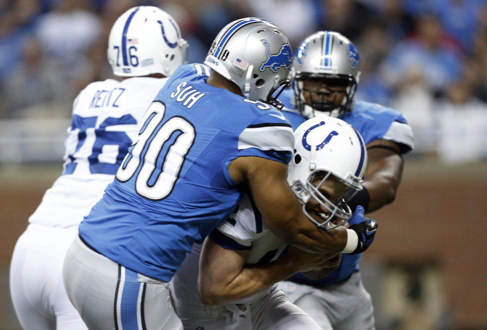 Photo - Detroit Lions defensive tackle Ndamukong Suh (90) sacks Indianapolis Colts quarterback Andrew Luck in the first quarter of an NFL football game at Ford Field in Detroit, Sunday, Dec. 2, 2012. (AP Photo/Rick Osentoski)