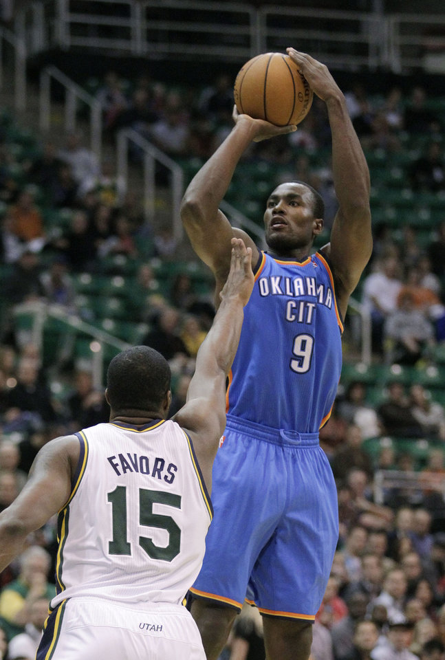 Photo - Oklahoma City Thunder center Serge Ibaka (9) shoots as Utah Jazz forward Derrick Favors (15) defends in the first quarter of a preseason NBA basketball game Friday, Oct. 12, 2012, in Salt Lake City. (AP Photo/Rick Bowmer) ORG XMIT: UTRB107