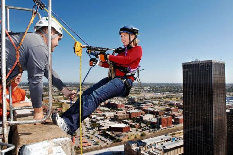 FUNDRAISER / FUNDRAISING / RAPPEL / RAPELLING FOR CHARITY: Angi Bruss is given final instructions as she begins her descent from the top of  SandRidge Building in downtown Oklahoma City Wednesday, Oct. 13, 2010.   Photo by Jim Beckel, The Oklahoman ORG XMIT: KOD