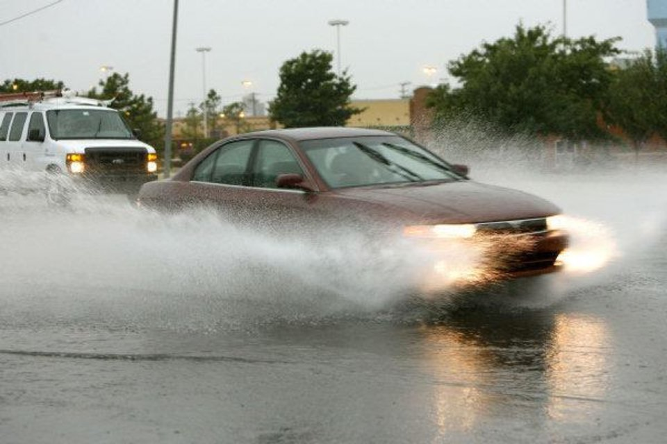Photo - Cars plow through deep water after a downpour at 33rd and Broadway in Edmond, OK, Thursday, Aug. 11, 2011. By Paul Hellstern, The Oklahoman ORG XMIT: KOD