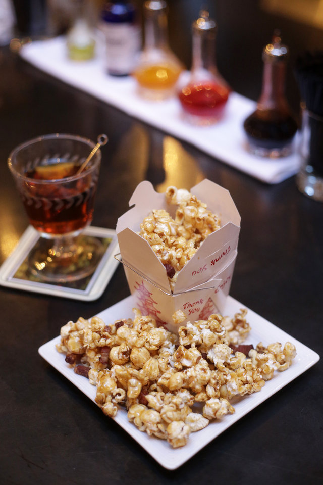 Photo - In this Monday, Dec. 30, 2013 photo, a plate of bacon popcorn, front, sits on a bar next to a cocktail called the