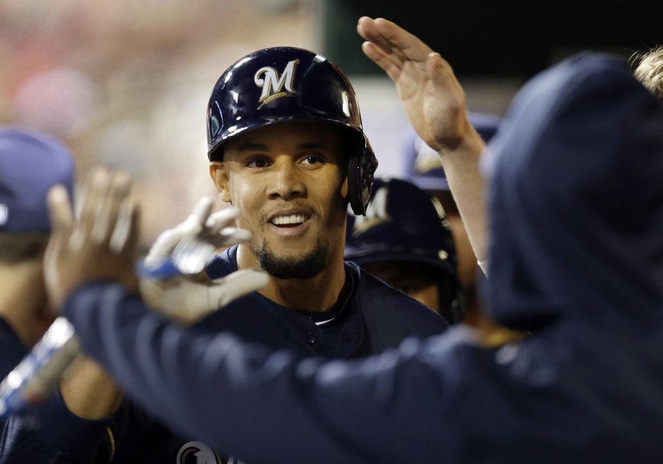 Photo - Milwaukee Brewers' Carlos Gomez is congratulated by teammates in the dugout after hitting a solo home run during the seventh inning of a baseball game against the St. Louis Cardinals, Tuesday, April 29, 2014, in St. Louis. (AP Photo/Jeff Roberson)