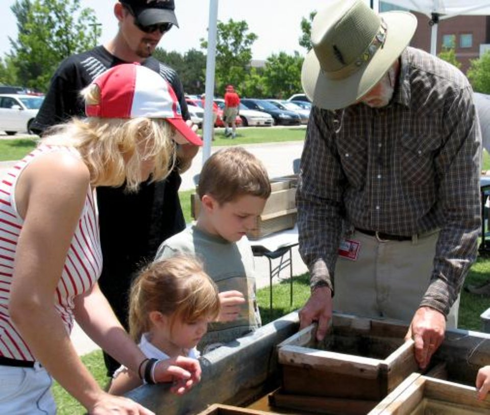 Volunteer Bill Dengler (right) shows visitors how to screenwash fossils Saturday, June 10, as a part of Dino Daze activities at the Sam Noble Oklahoma Museum of Natural History in Norman. Community Photo By: Scott Butcher Submitted By: Linda, Norman