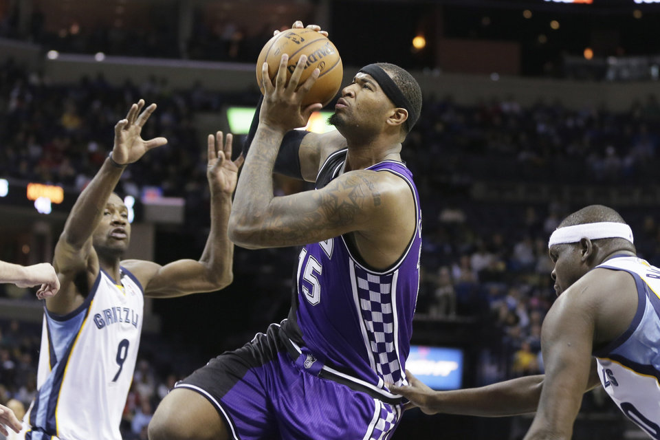Sacramento Kings' DeMarcus Cousins, center, goes to the basket between Memphis Grizzlies' Tony Allen, left, and Zach Randolph, right, during the first half of an NBA basketball game in Memphis, Tenn., Tuesday, Feb. 12, 2013. (AP Photo/Danny Johnston)