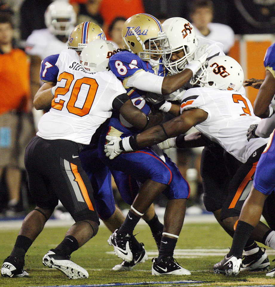 A group of Cowboys, including Larry Stephens (20) and Isaac Maselera (3) stop TU's Freeman Kelley (84) on a kick return in the second quarter during a college football game between the Oklahoma State University Cowboys and the University of Tulsa Golden Hurricane at H.A. Chapman Stadium in Tulsa, Okla., Sunday morning, Sept. 18, 2011. Photo by Nate Billings, The Oklahoman