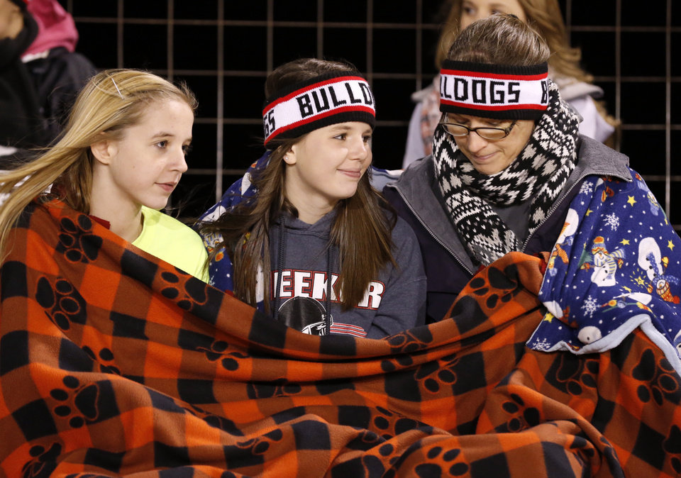 Photo - Meeker fans Mackenzie Gilbreath, 12, Katelyn Ferguson, 15, and Angella Dushack huddle for warmth as the Millwood Falcons play the Meeker Bulldogs in state high school football playoffs on Friday, Nov. 29, 2013, in Meeker, Okla.  Photo by Steve Sisney, The Oklahoman